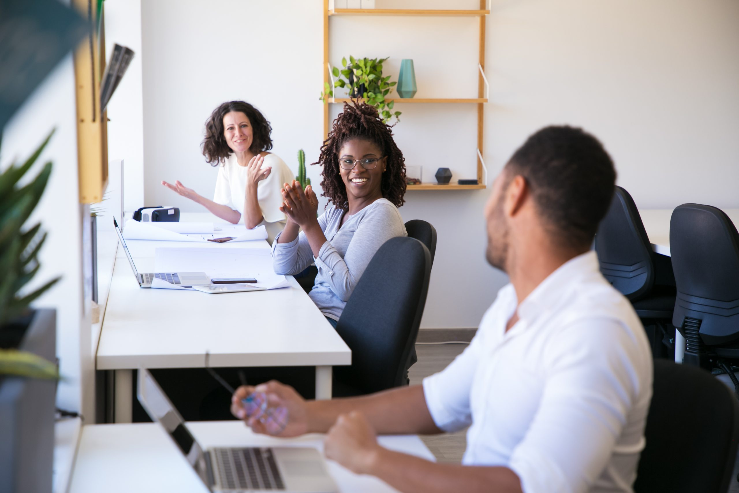 Cheerful colleagues communicating at workplace